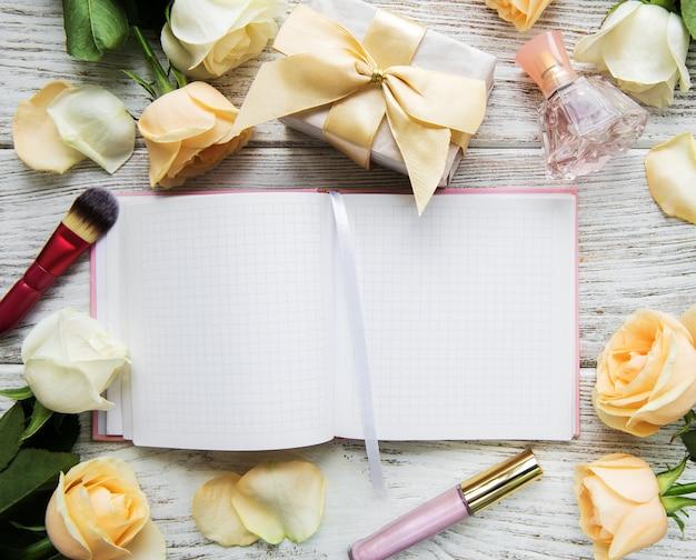 Notebook, rose e cosmetici su un vecchio tavolo di legno