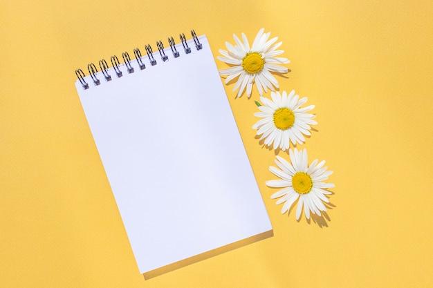 Notebook su una spirale con un foglio vuoto e fiori di camomilla su uno sfondo giallo brillante.