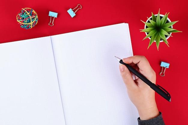 Notebook su uno sfondo rosso.