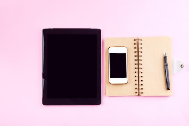Notebook, tablet, penna e smart phone su uno sfondo rosa pastello