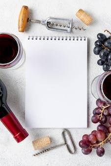 Notebook vista dall'alto con cornice di uva e vino