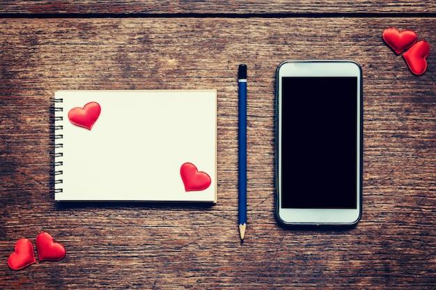 Notebook vuota, matita e cuore rosso sul tavolo di legno con schermo di spazio di copia vuoto del telefono per la vostra pubblicità. sfondo di san valentino.
