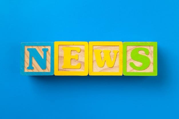 Notizia. blocchi alfabeto colorato in legno sul blu
