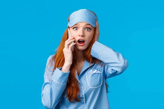 Notizie terribili. giovane ragazza turbata e preoccupata che sente accadere qualcosa di brutto, parla al telefono, tocca la testa frustrata, ansima la mascella di goccia e guarda sbalordita, in piedi parete blu
