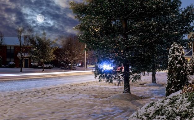 Notte dei fari dell'automobile di inverno su una strada di notte nevosa