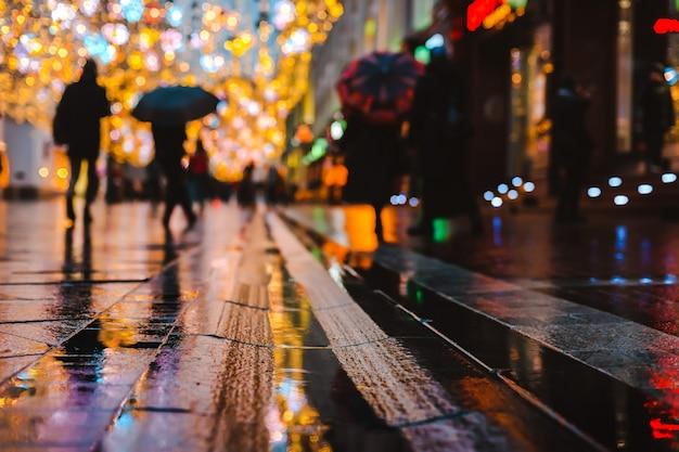 Notte di pioggia in una grande città, riflessi di luci sul fondo stradale bagnato.