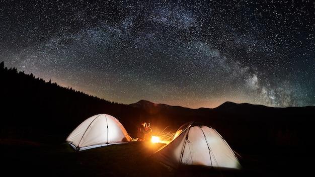 Notte in campeggio. coppia i turisti che si siedono e che abbracciano ad un fuoco di accampamento vicino a due tende illuminate