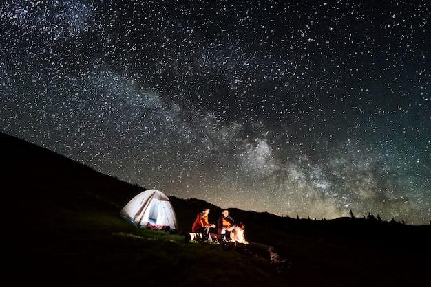 Notte in campeggio. turisti romantici delle coppie che godono ad un falò vicino alla tenda illuminata sotto il bello cielo notturno pieno di stelle e via lattea