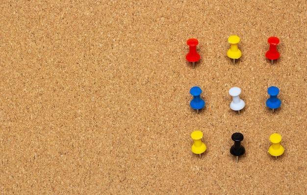 Nove pulsanti appuntati colorati su una tavola di sughero