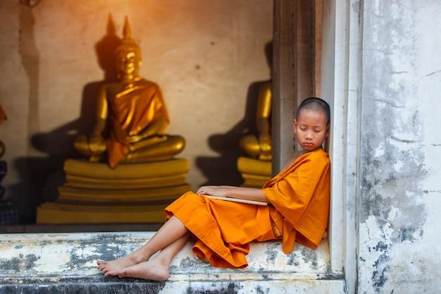 Novizio che dorme sulla terrazza dopo una dura disciplina di studio al di fuori di the buddha status