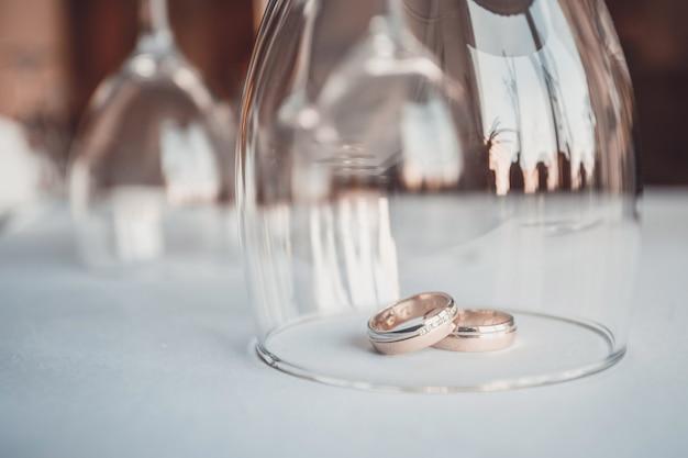 Nozze . giorno del matrimonio. due anelli di nozze d'oro isolato su bianco vicino. novelli sposi