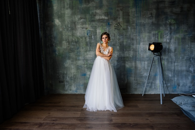Nozze. la sposa in bello vestito all'interno nell'interno bianco dello studio gradisce a casa.