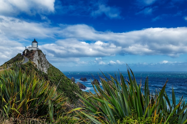 Nugget point lighthouse e bellissimo paesaggio naturale con nuvole nel cielo