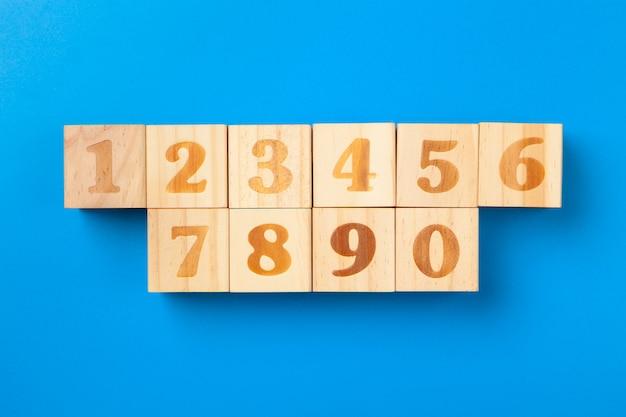 Numeri. blocchetti di alfabeto variopinto di legno su fondo blu, disposizione piana, vista superiore.