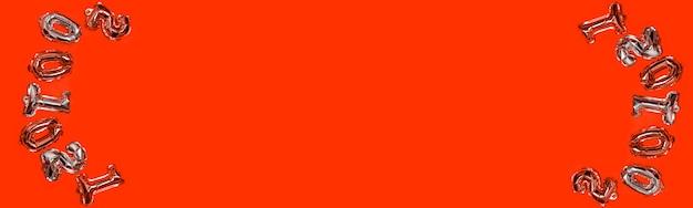Numeri di aria oro e argento palloncini su uno sfondo rosso. composizione in festa con copyspace, vista dall'alto.