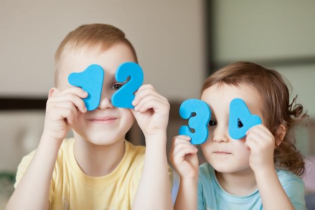 Numeri numerici educativi in mani di un bambino. insegnare ai numeri dei bambini.