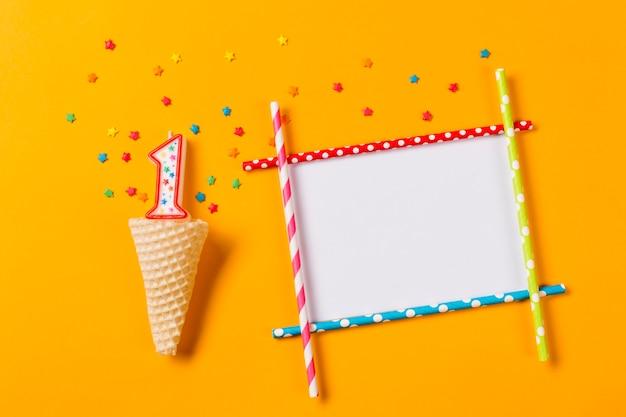 Numero 1 candela con stella colorata spruzza sopra il cono di cialda e cornice vuota su uno sfondo arancione