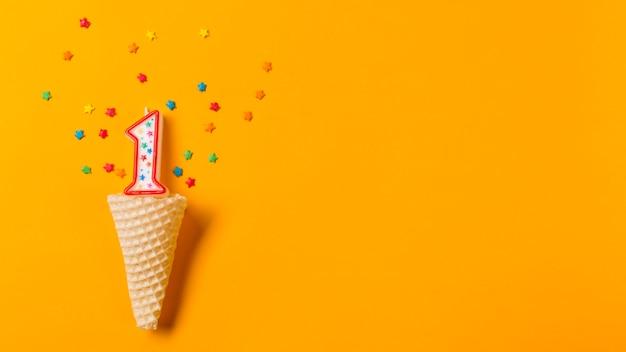 Numero 1 candela con stella colorata spruzza sopra il cono di cialda su uno sfondo arancione