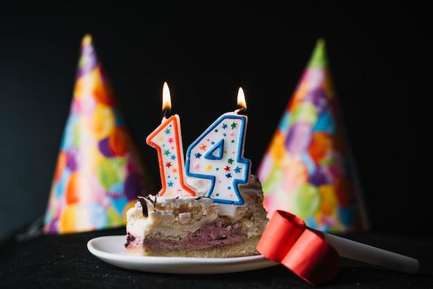 Numero 14 candela accesa compleanno sulla fetta di torta con cappello di partito e ventilatore di corno di partito