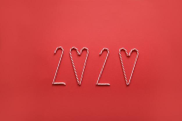 Numero 2020 realizzato con varie caramelle a cono natalizio su rosso. capodanno minimo. creativo sfondo piatto laico.