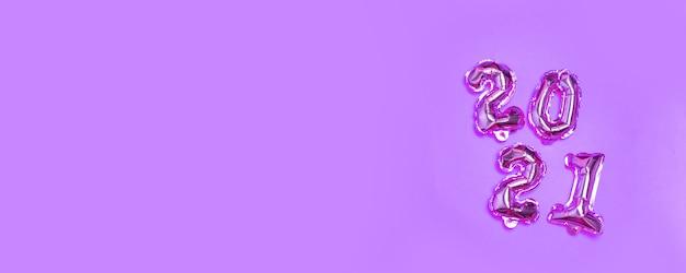 Numero 2021 palloncini su uno sfondo lilla con spazio di copia.