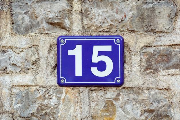 Numero civico blu quindici su un muro di pietra