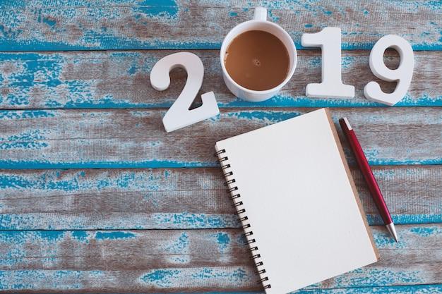 Numero di legno e caffè caldo con testo 2019 e notebook sulla tavola di legno blu rustico