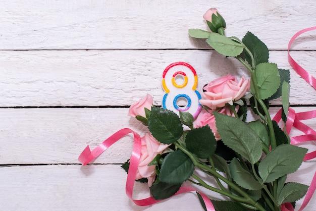 Numero otto come simbolo di una vacanza 8 marzo e rose rosa sul tavolo di legno. biglietto di auguri con fiori per la festa della donna internazionale. copia spazio