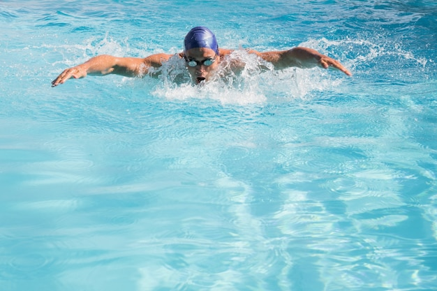 Nuotatore adatto che fa il colpo di farfalla nella piscina