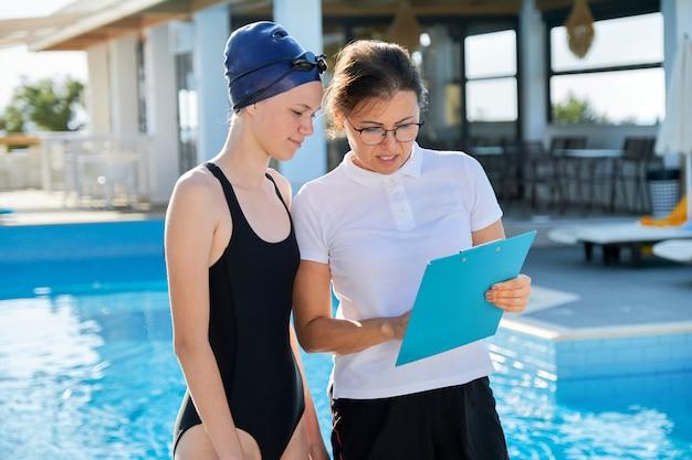 Nuotatore dell'adolescente della ragazza in cappuccio del costume da bagno di sport con l'addestratore della donna vicino allo stagno all'aperto