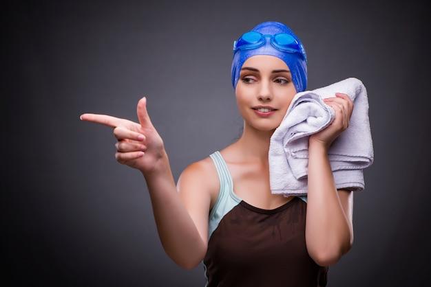 Nuotatore della donna contro fondo grigio