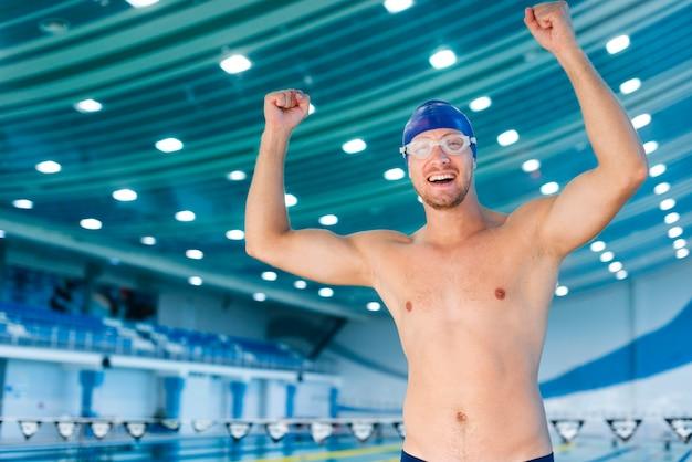 Nuotatore felice dell'uomo che solleva le sue mani