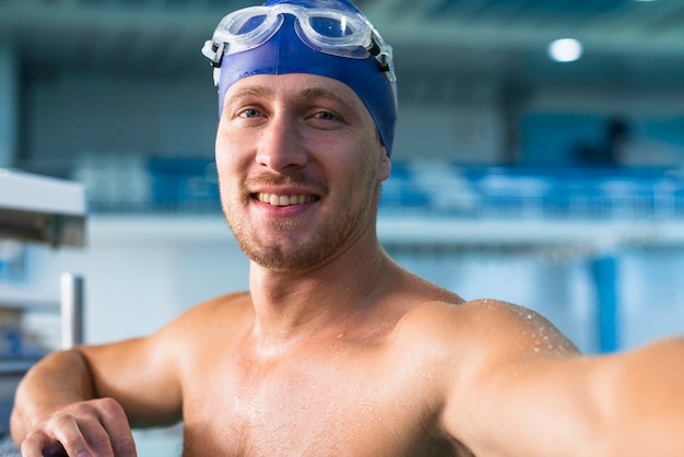 Nuotatore maschio atletico che prende un selfie