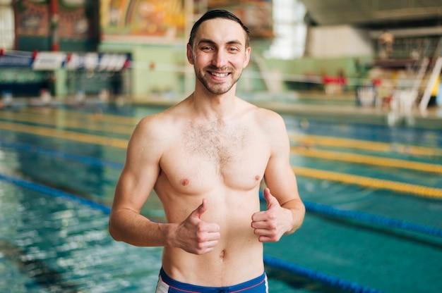 Nuotatore maschio dell'angolo alto che mostra segno giusto