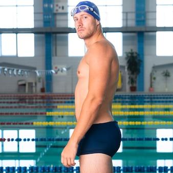Nuotatore maschio di attractiv che si siede sul bordo dello stagno