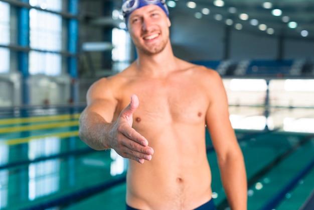 Nuotatore maschio sorridente che dà la sua mano