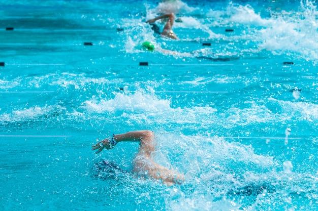 Nuotatori maschi che lavorano sul loro stile libero a nuotare in una piscina locale
