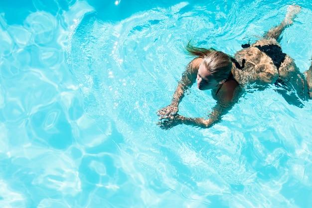 Nuoto adatto della donna nello stagno in un giorno soleggiato