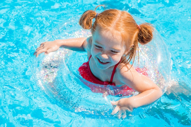 Nuoto della bambina nello stagno di estate