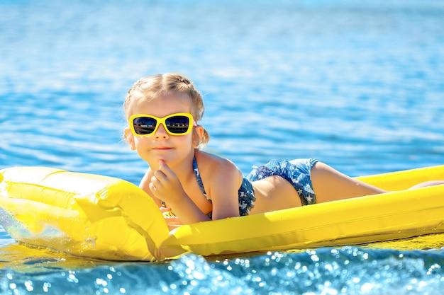 Nuoto della bambina sul materasso gonfiabile della spiaggia.