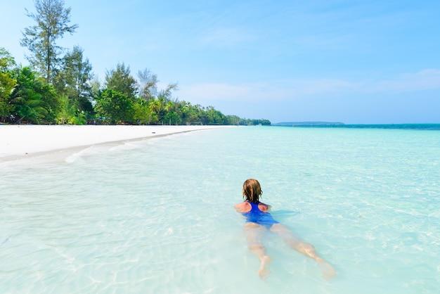Nuoto della donna in acqua trasparente del turchese del mar dei caraibi. spiaggia tropicale in kei islands moluccas, destinazione turistica di estate in indonesia.