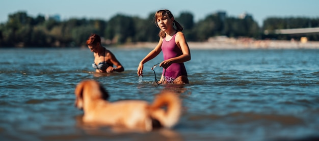 Nuoto della ragazza nel fiume con il suo cane