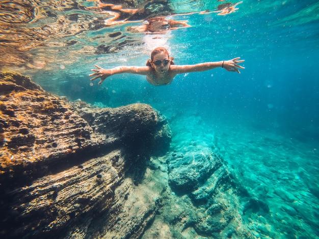 Nuoto della ragazza nel mare dalla scogliera