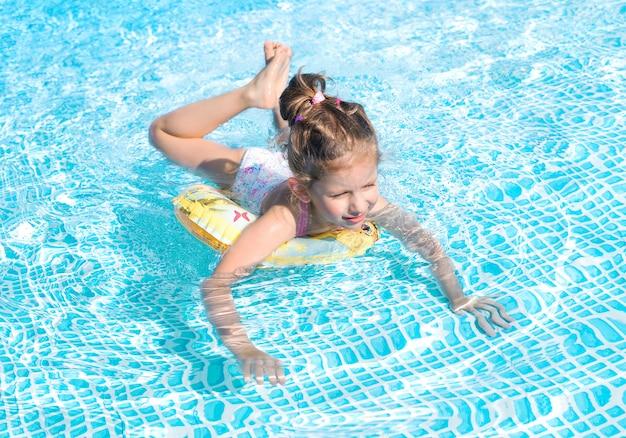 Nuoto divertente della bambina nello stagno
