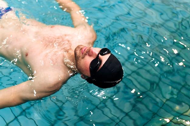 Nuoto maschio ad alto angolo sul retro