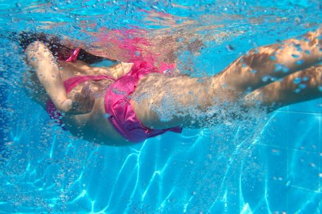 Nuoto rosa della bambina del bikini subacqueo nello stagno
