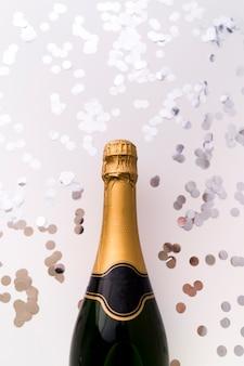 Nuova bottiglia di champagne e coriandoli rotondi d'argento su fondo bianco