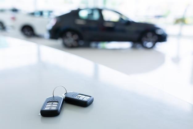 Nuova chiave negli autosalone con due nuove chiavi remote posizionate sul tavolo di lavoro nel nuovo autosalone.