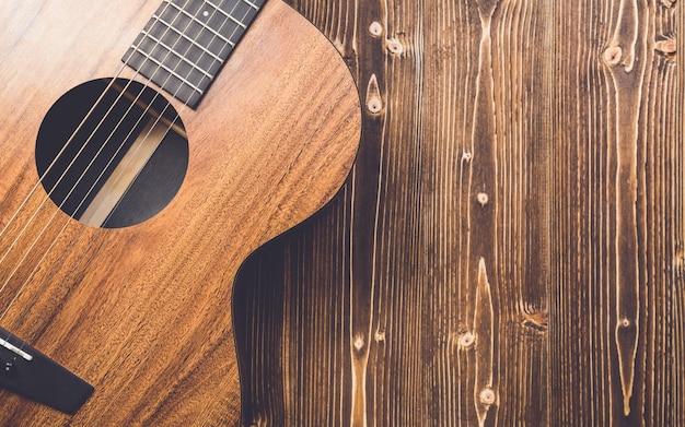 Nuova chitarra marrone su tavola di legno