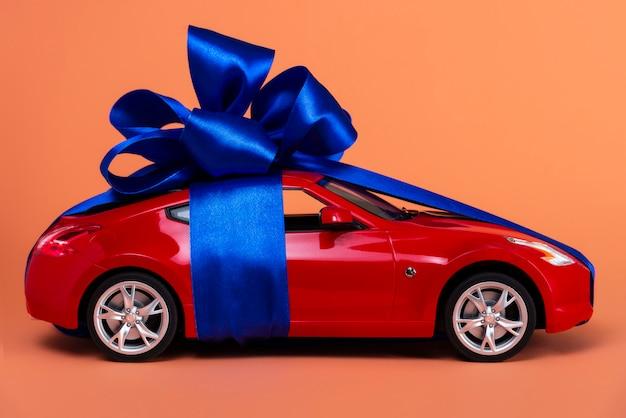 Nuova macchina rossa con un fiocco blu come regalo sul corallo